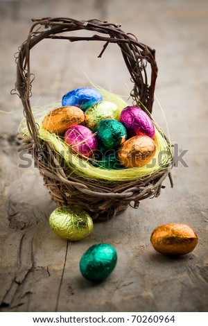 Colorful chocolate easter eggs in brown basket - stock photo