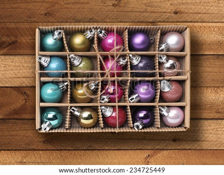 Colorful Christmas balls in cardboard box on wooden background - stock photo