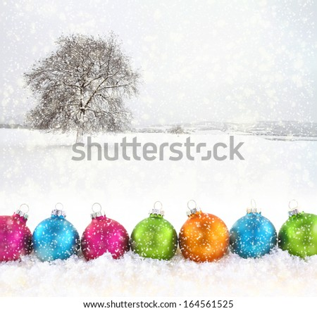 Colorful Christmas balls with snowfield as background - stock photo