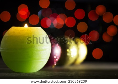 Colorful Christmas baubles on wooden background with green candle in front and red bokeh background in dark