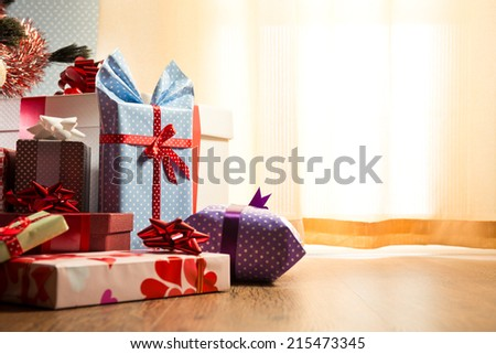 Colorful christmas gifts with ribbon on the floor, assorted colors and sizes. - stock photo