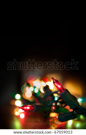 colorful christmas lights running along a mantelpiece, selective focus on single light isolated on black background