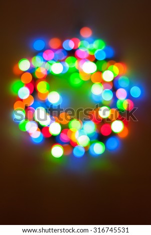 Colorful Christmas lights wreath bokeh - A bright circular multicolor bokeh in the form of a Christmas wreath created by a set of de-focused lights. - stock photo