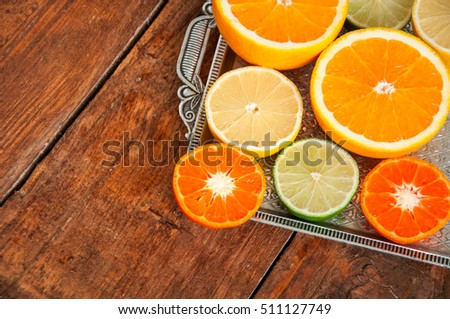 Colorful citrus fruits. Lemon, orange, tangerine and lime in a vintage tray on a wooden table. Copy space. Close up.