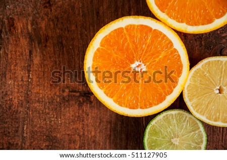 Colorful citrus fruits. Lemon, orange, tangerine and lime on a wooden table. Top view. Copy space.Close up.