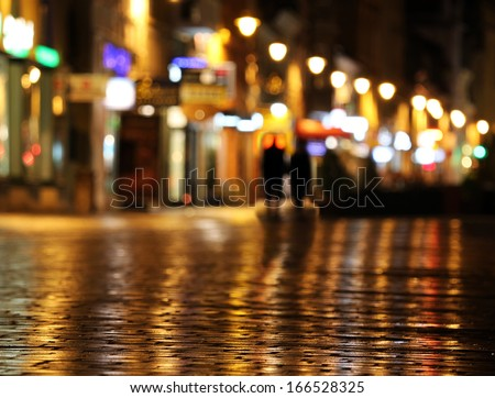Colorful city lights and shadow of couple walking mirrored in the wet street
