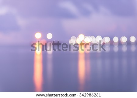 Colorful city lights with bokeh effect reflected over sea background at dusk - stock photo
