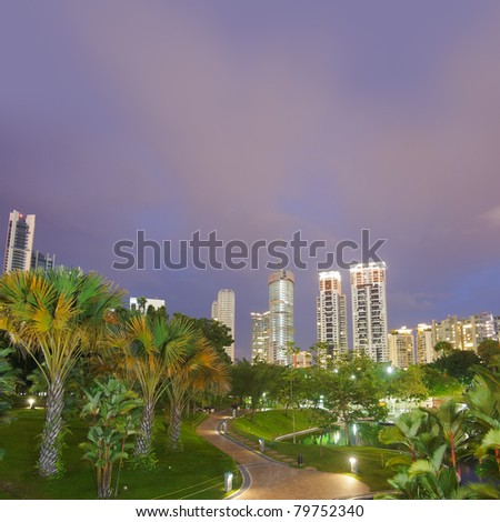 Colorful city night scene with modern buildings and green trees in park In Kuala Lumpur, Malaysia, Asia. - stock photo