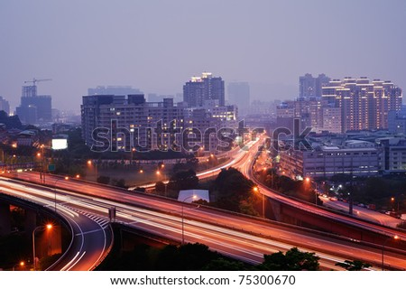 Colorful city night with buildings and bridge under blue sky in Taipei, Taiwan, Asia. - stock photo