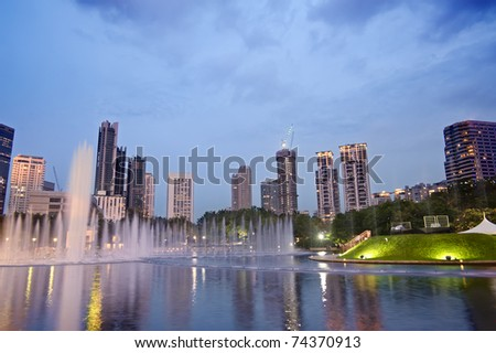 Colorful city night with buildings and fountain in Kuala Lumpur, Malaysia, Asia. - stock photo