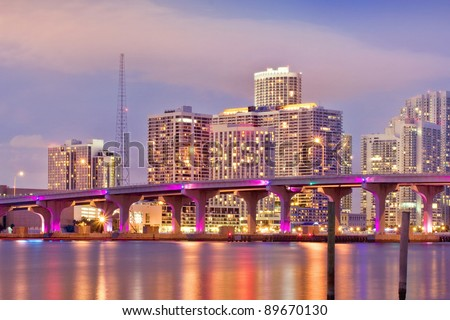 Colorful Cityscape of Miami Florida, downtown buildings and MacArthur Causeway bridge illuminating Biscayne bay at sunset. - stock photo