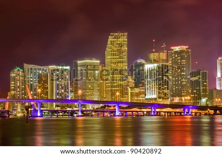 Colorful Cityscape of Miami Florida, downtown buildings and MacArthur Causeway bridge illuminating Biscayne bay after sunset. - stock photo