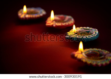 Colorful clay diya lamps lit during diwali celebration - stock photo