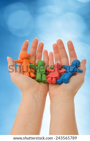 Colorful clay people in woman palm - against blurred blue background - stock photo
