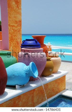 colorful clay pots with blue caribbean ocean - stock photo