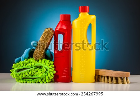 colorful cleaning equipment on table and blue background - stock photo