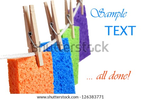 Colorful cleaning sponges hanging on clothesline to drip dry.  Macro on  white background with copy space.  Shallow dof with selective focus on orange sponge. Concept - all done with spring cleaning! - stock photo