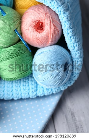 Colorful clews, napkin and crochet hook in basket on wooden background