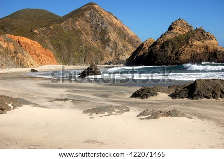 Colorful cliffs of secluded Julia Pfeiffer State Beach in sunset light.  Big Sur, California - stock photo