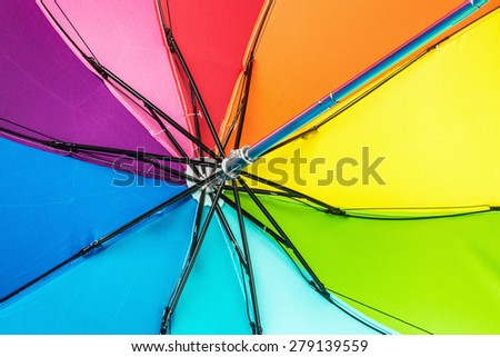 Colorful close up abstract of rainbow umbrella. Focus on the spokes of the umbrella - stock photo