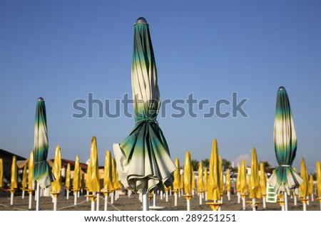 Colorful closed parasols on Mediterranean beach - stock photo