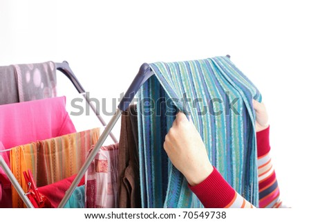 colorful clothes hanged for drying after laundry clothes airer, clothes dryer isolated on white and woman hand - stock photo