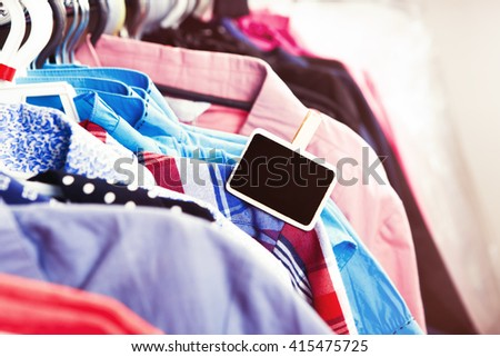 Colorful clothes hanging on a hanger and tag on it - stock photo