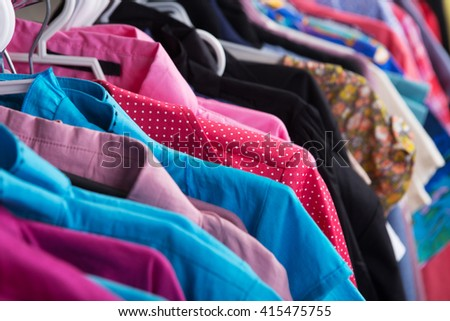 Colorful clothes hanging on the rack - stock photo