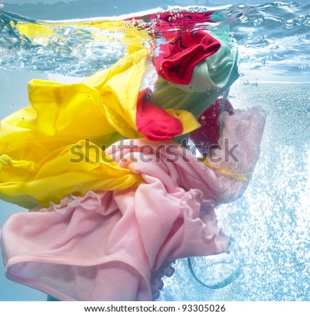 Colorful clothes in the washing machine - stock photo