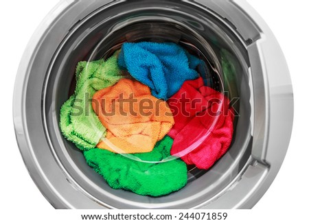 colorful clothes in the washing machine on a white background - stock photo