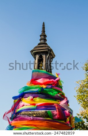 Colorful clothes wrap the shelter of buddha image. - stock photo