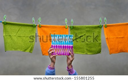 Colorful clothespins and towels on rope - stock photo