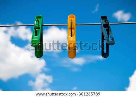 colorful clothespins on a background of blue sky and white clouds - stock photo