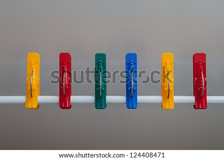 Colorful clothespins on a white plate - stock photo