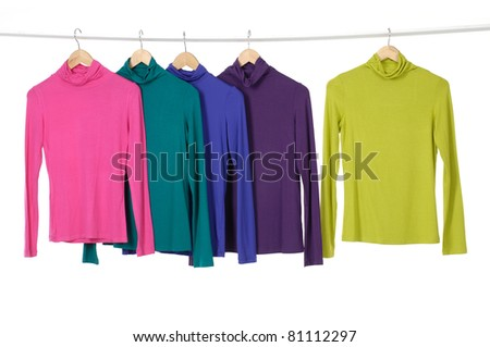 colorful clothing hanging on wooden hangers - stock photo