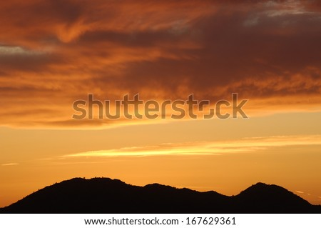 Colorful cloud layers at sunset with silhouetted hill