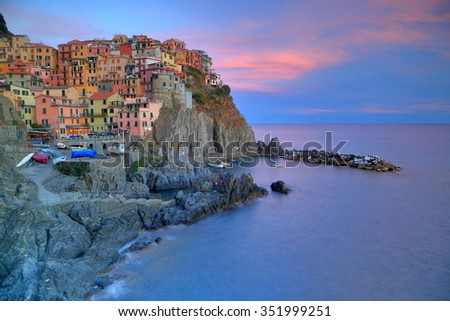 Colorful clouds above the sea near the old town and harbor of Manarola, Cinque Terre, Italy