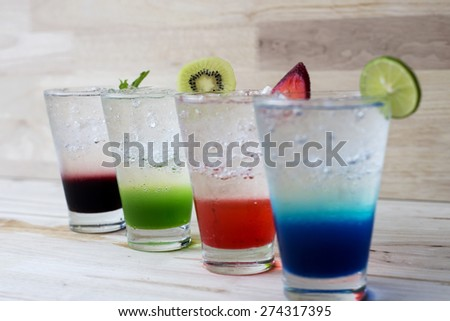 Colorful cocktail drink on wood table - stock photo