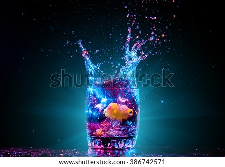 colorful cocktail in glass with splashes and lemon on dark background. Party club entertainment. Mixed light - stock photo