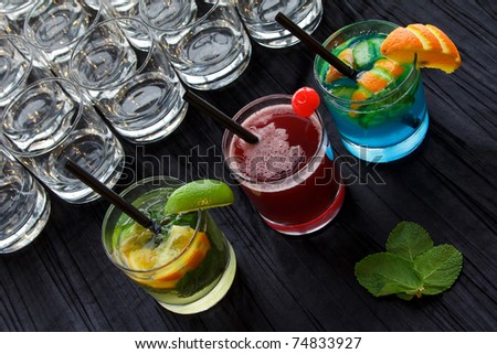 Colorful cocktails on a black tablecloth.