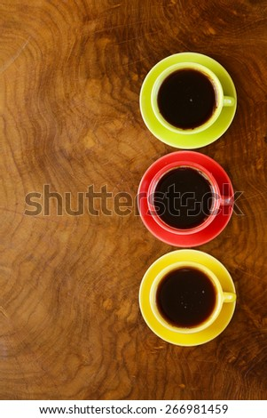 colorful coffee cups on a wooden background - stock photo