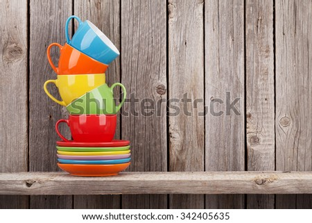 Colorful coffee cups on shelf against rustic wooden wall with copy space - stock photo
