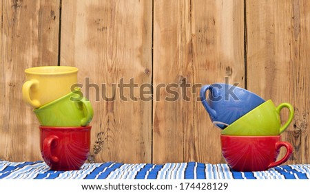 Colorful coffee cups on stripe tablecloth over wood background  - stock photo