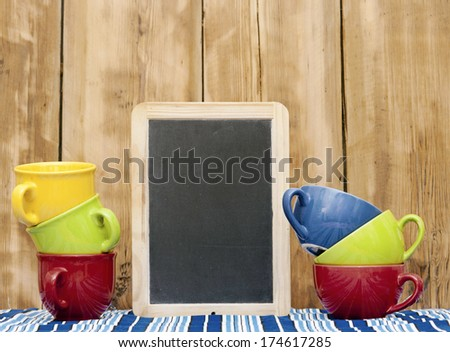 Colorful coffee cups on stripe tablecloth with blank small blackboard over wood background - stock photo