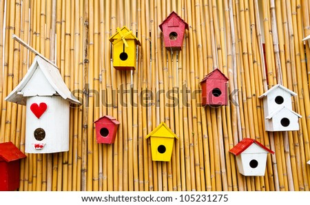 Colorful collection of birdhouses on wood wall - stock photo
