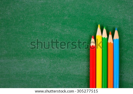 Colorful Colored Pencils or Crayons on green school board - stock photo
