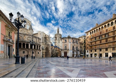 Colorful composition of the main Virgin square in Valencia, Spain, with the historical cathedral Seu end basilica and white clouds in blue sky