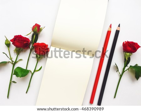 Colorful composition with sketchbook, red roses and pencils. Flat lay on white table, top view, overhead view with copy space