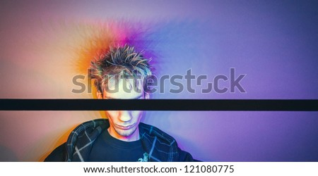 Colorful conceptual photograph of a young guy hiding his eyes with a black stick. Colorful background. - stock photo