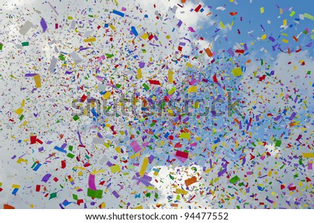 Colorful confetti flying through the air against blue sky - stock photo